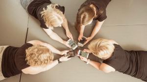 Diginaiset ympyrässä puhelimet kädessä